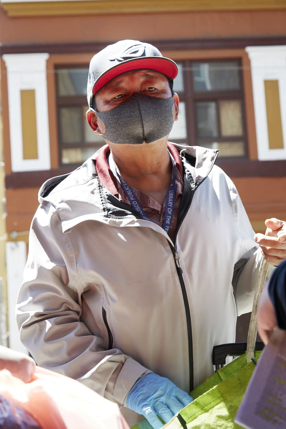 Southeast Asian American male elder wearing a facemask and rubber gloves during a covid-19 food drive in tenderloin, san francisco