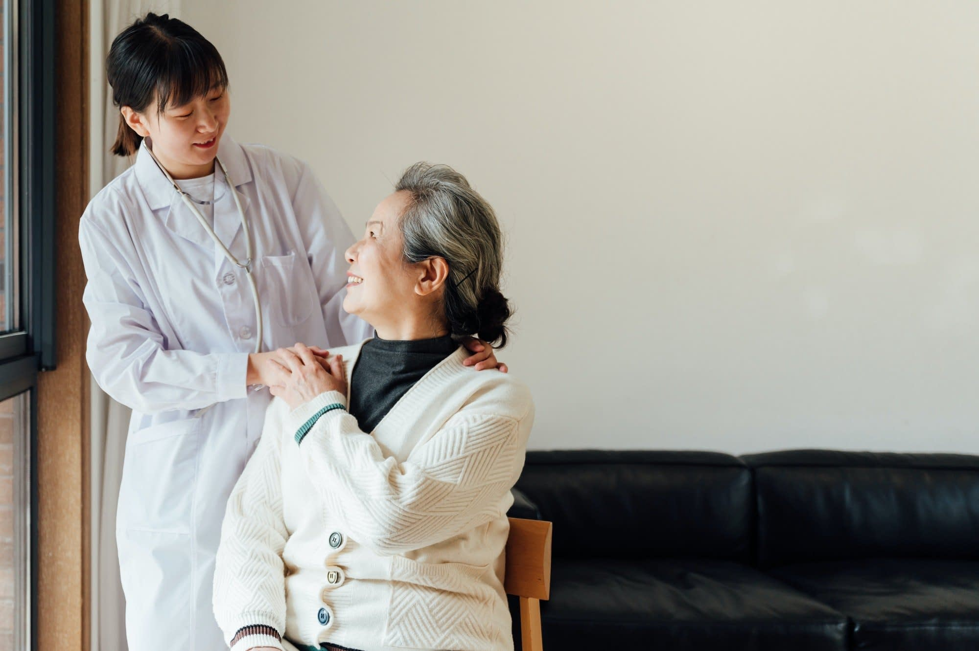 Senior woman with young female doctor at home