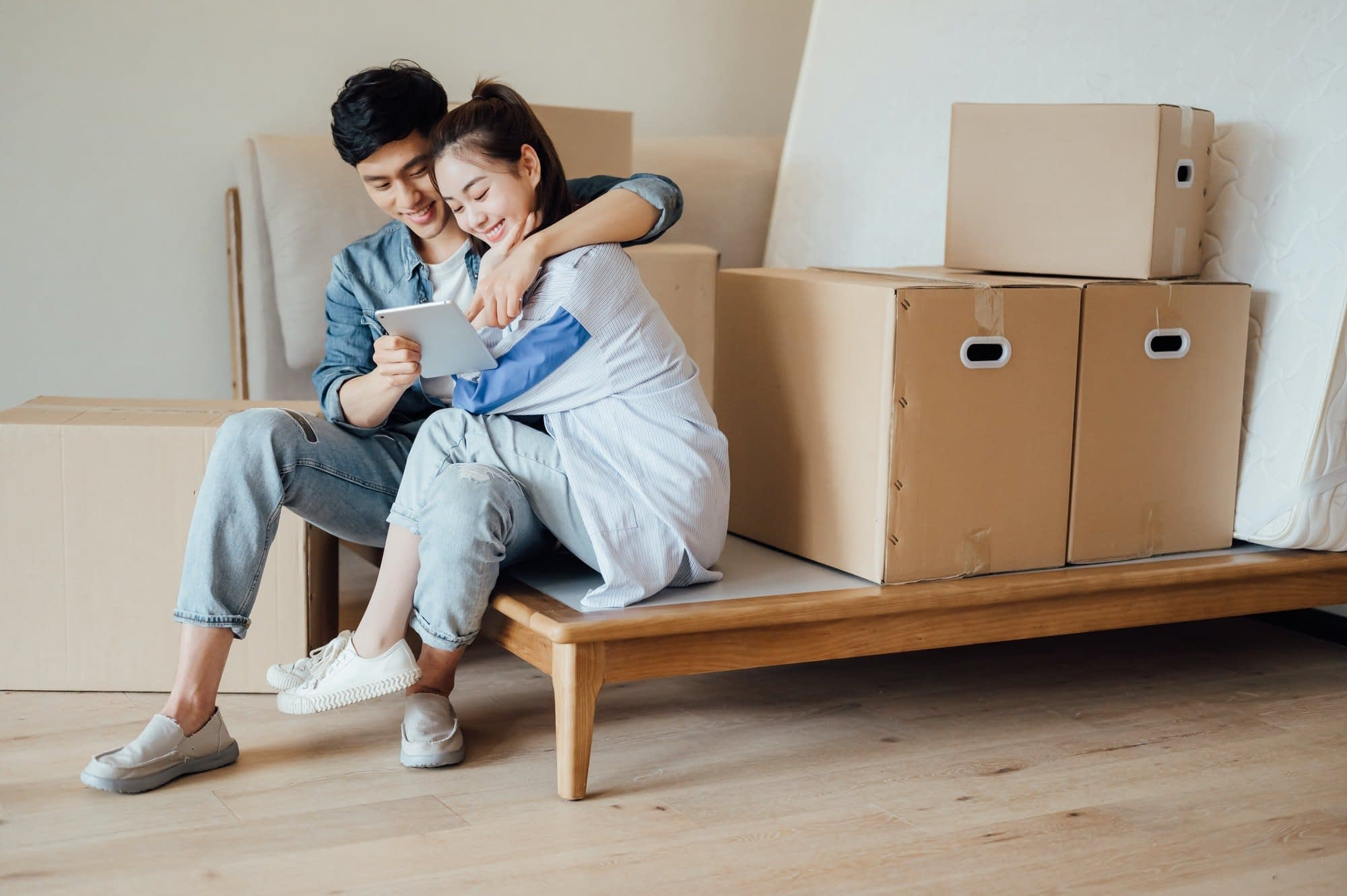 Young couple using ipad during moving house
