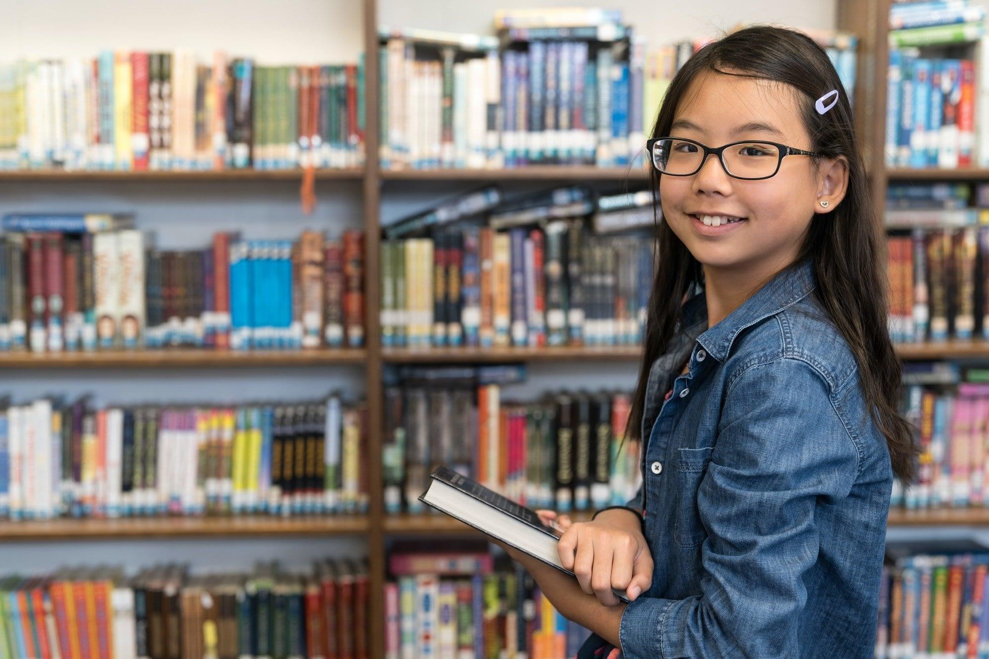Asian teenage girl with eyeglasses in school library