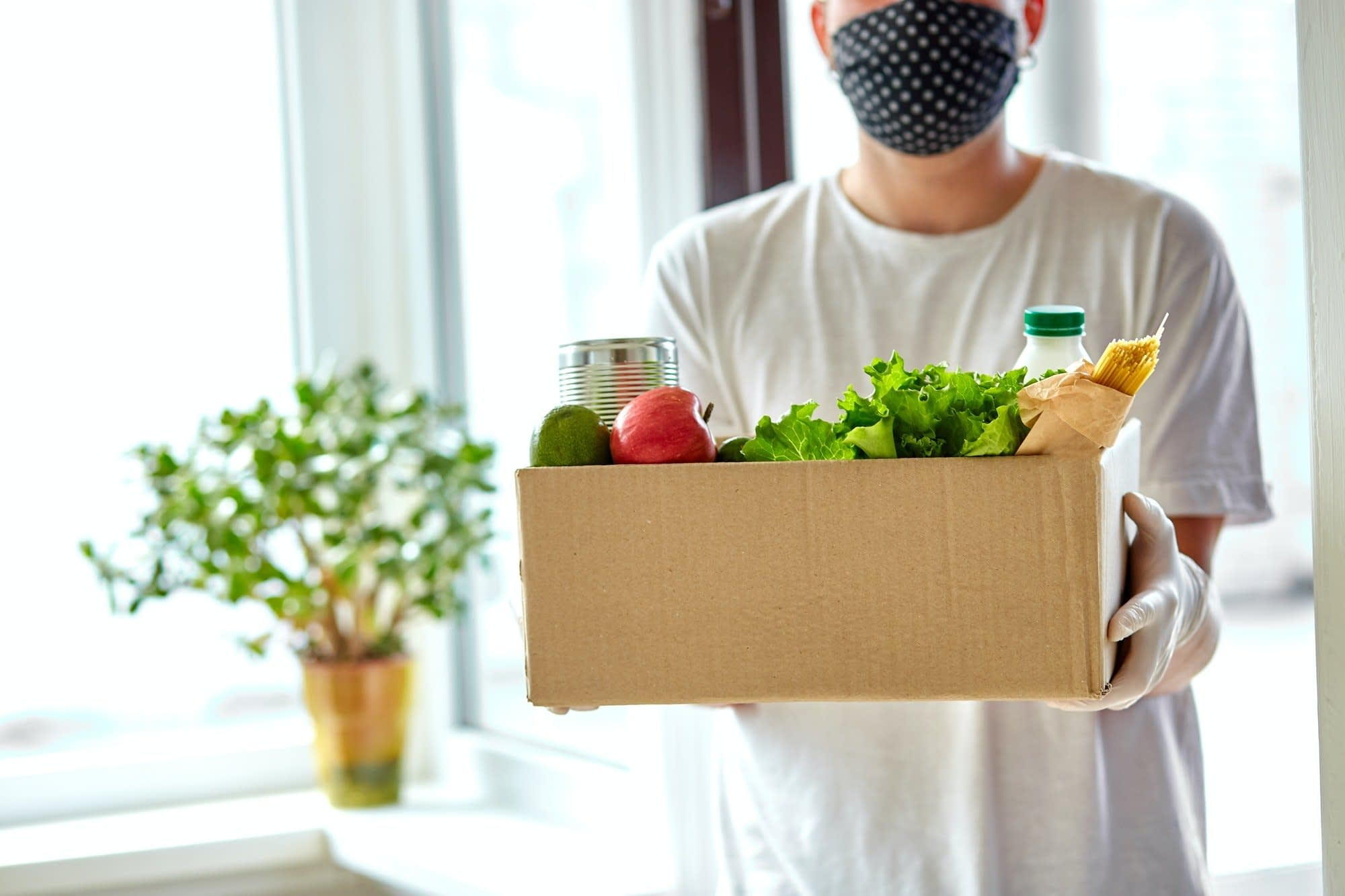 Volunteer in the protective medical mask and gloves delivery donation box at home