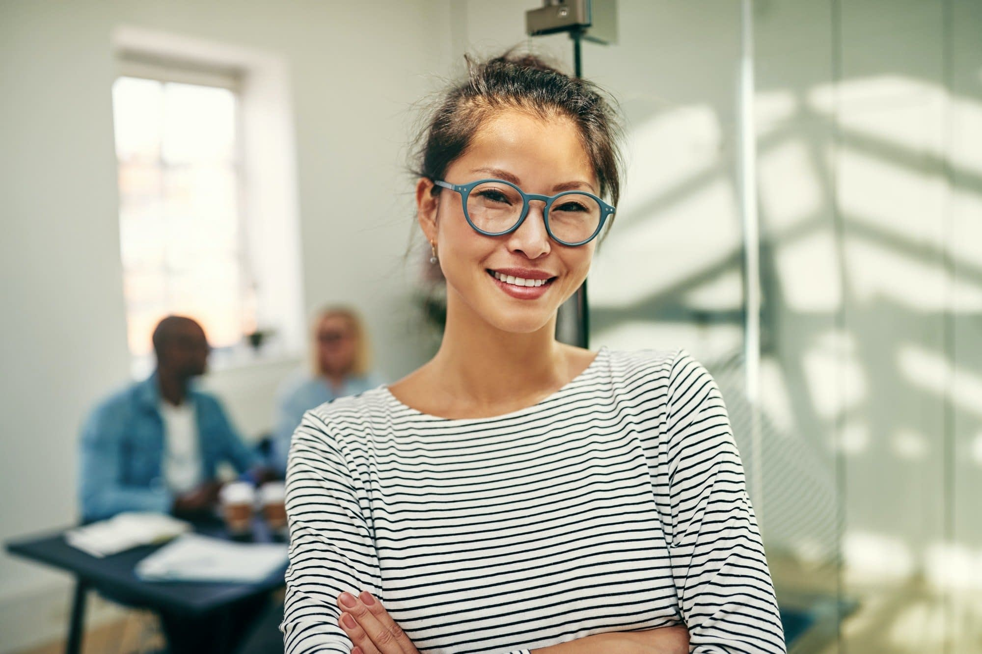 Young Asian businesswoman smiling confidently in a modern office